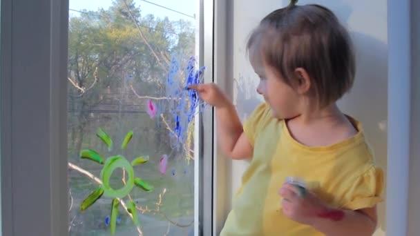 Pozitivní holčička kreslí na okno. Koncept děcka doma. Karanténa