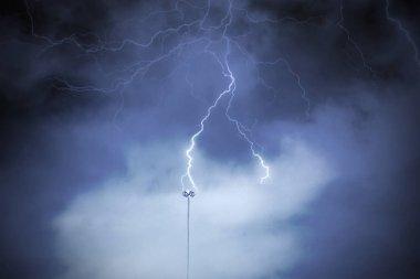 Lightning rod against a cloudy dark sky.