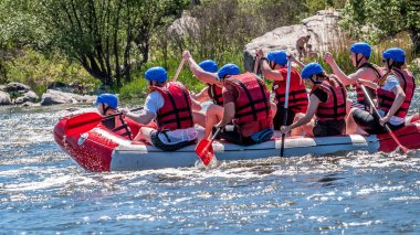 Myhiya, Ukraine - May 1, 2018: Place for recreation, ecological water tourism. Rafting, kayaking. Close-up view of oars with splashing water. A group of people with a child on a rubber inflatable boat