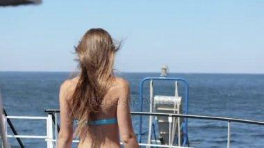 Krásný model v bikinách stojící zády na lodi