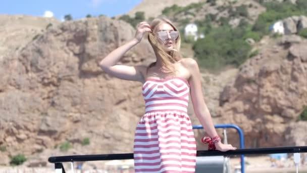 Sexy blondýnka s dlouhými vlasy v šatech a sluneční brýle, cestující na palubě lodi v moři