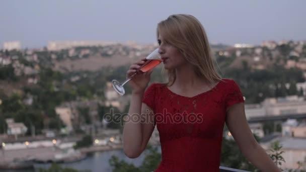Verführerische Blondine im roten Abendkleid Champagner auf der Terrasse im Freien im Restaurant trinken