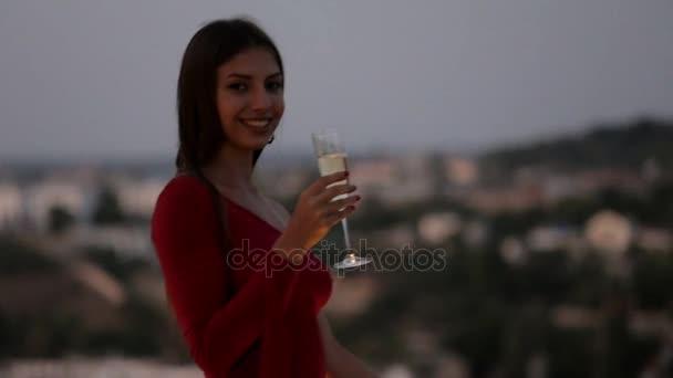 Attraktive Brünette in einem roten Kleid Champagner auf der Terrasse im Restaurant trinken