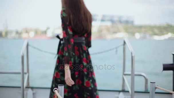 Nádherná brunetka v dlouhých černých šatech, stojící na palubě lodi