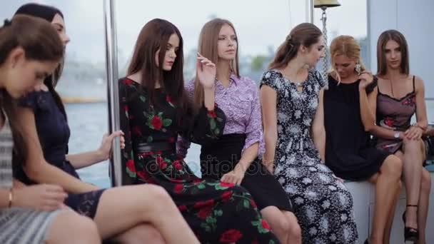 Okouzlující mladé ženy v šatech sedí na okraji lodi do moře