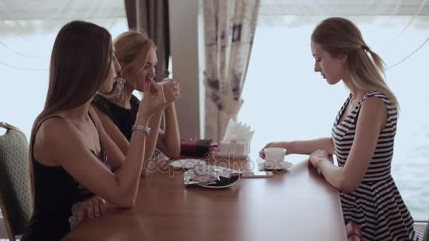 Tři krásné dívky, sedící u stolu na Radě přívozu u okna