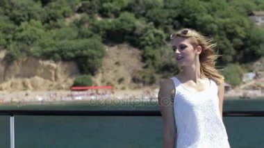 Cute blonde in dress sitting on a boat in windy weather