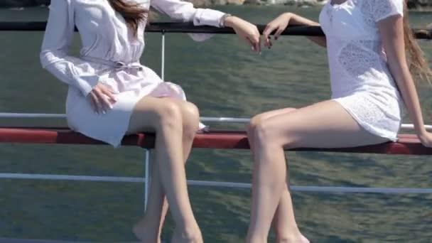 Dvě krásné modely v bílém světle sundresses sedí na palubě lodi