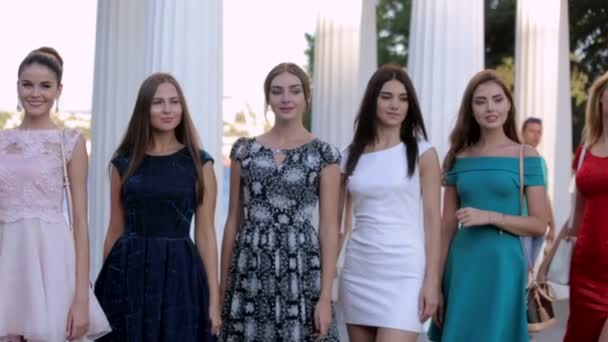 Group of beautiful girls posing in a dresses while standing in the street