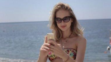 Girl in bikini doing photos to the phone