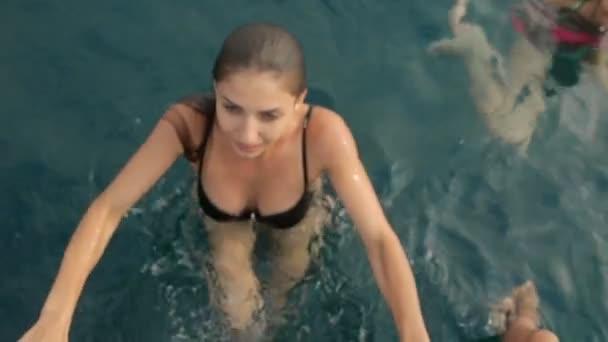 attraktive junge Frau im Bikini klettert auf ein Boot aus dem Meer