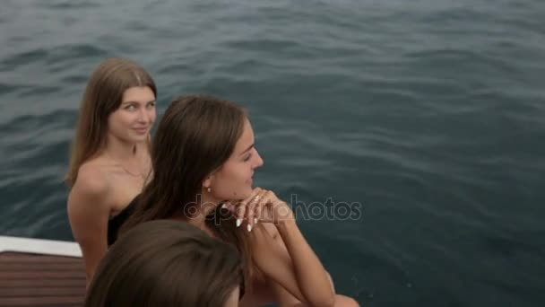 Krásné modelky v bikinách, sedí na okraji lodi