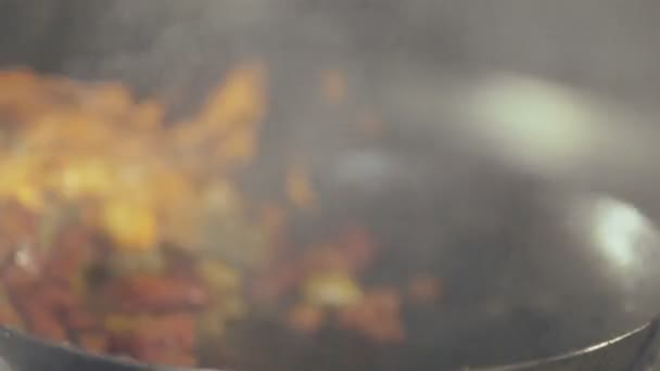 Chef in a kitchen cooking flambe style close-up.