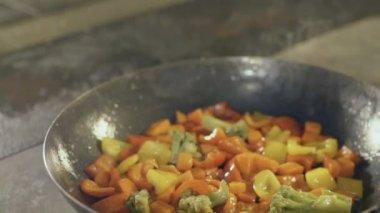 Fried vegetables in a griddle, slow motion