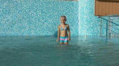 Malá holčička v plavkách blbnout v plaveckém bazénu