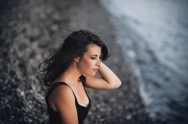 Amazing girl in the black dress sitting on the shore of the beach