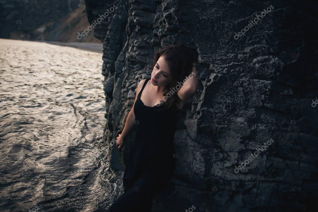 Seductive girl in the black dress standing leaning against the rock