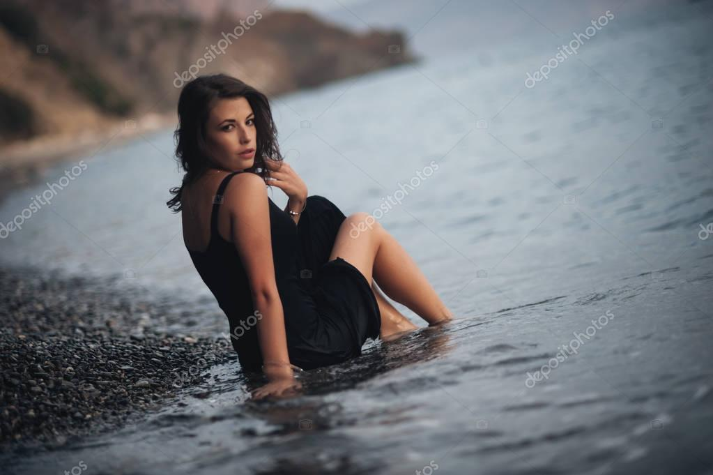Beautiful girl wearing the black dress lying on the pebbles on the beach in the waves