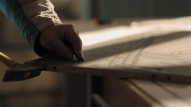 Ein Mann baut Möbel mit Hammer und Nägeln