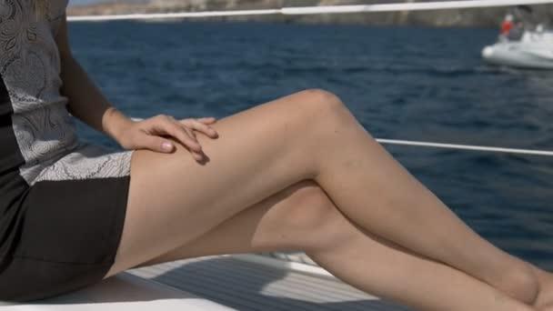 Fiatal nő feküdt a jacht nap barnító szexi lábak