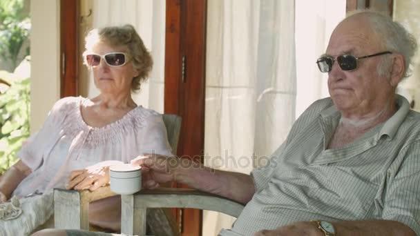 Pár starších lidí ve sluneční brýle sedí v přední dvoře svého domu