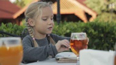 Holčička s dvěma pletence sedět u stolu ve venkovní kavárně