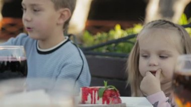 Little girl eating sauce from the cheesecake in the childrens outdoors cafe