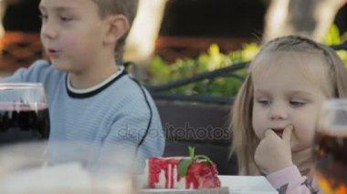 Malá holčička jíst omáčka ze tvarohový koláč v dětské venkovní kavárna