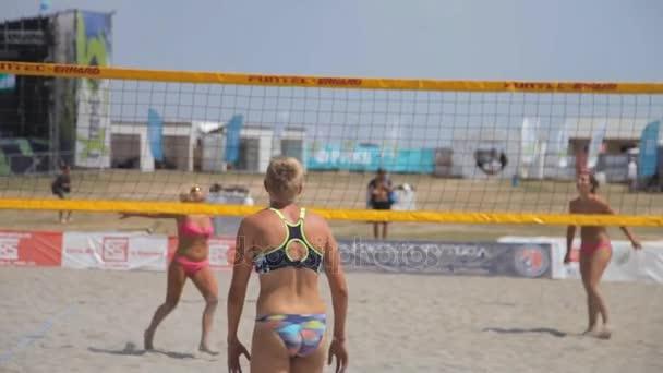 Čtyři sportovní dívky v plavkách hrát volejbal na pláži na 30 července v Olenevka