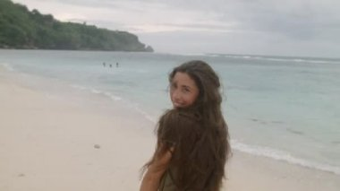 Happy tanned girl with long hair walking along the sandy beach