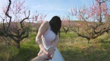 Girl in love leads the guy through the flowering garden