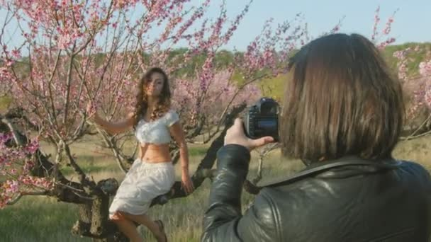 Photographer shoots model in the blossoming peach orchard