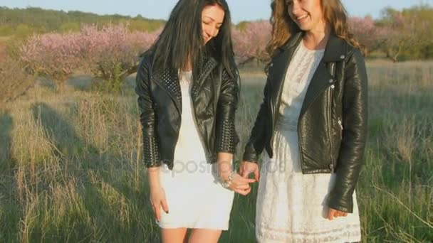 Two beautiful girls in dresses and leather jackets are fooled and hugging while standing in the field