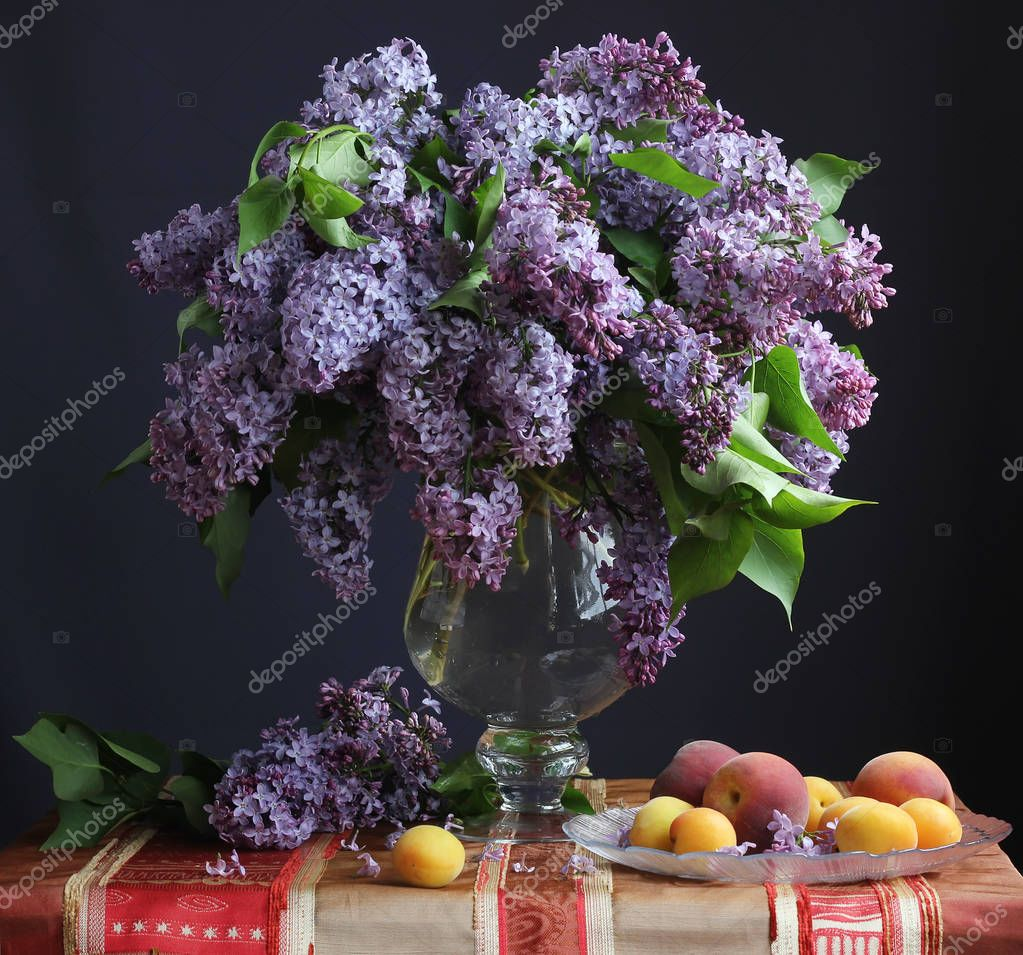 Still life with lilacs in a vase and fruit