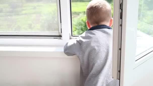 Malý chlapec vypadá zasněně z okna