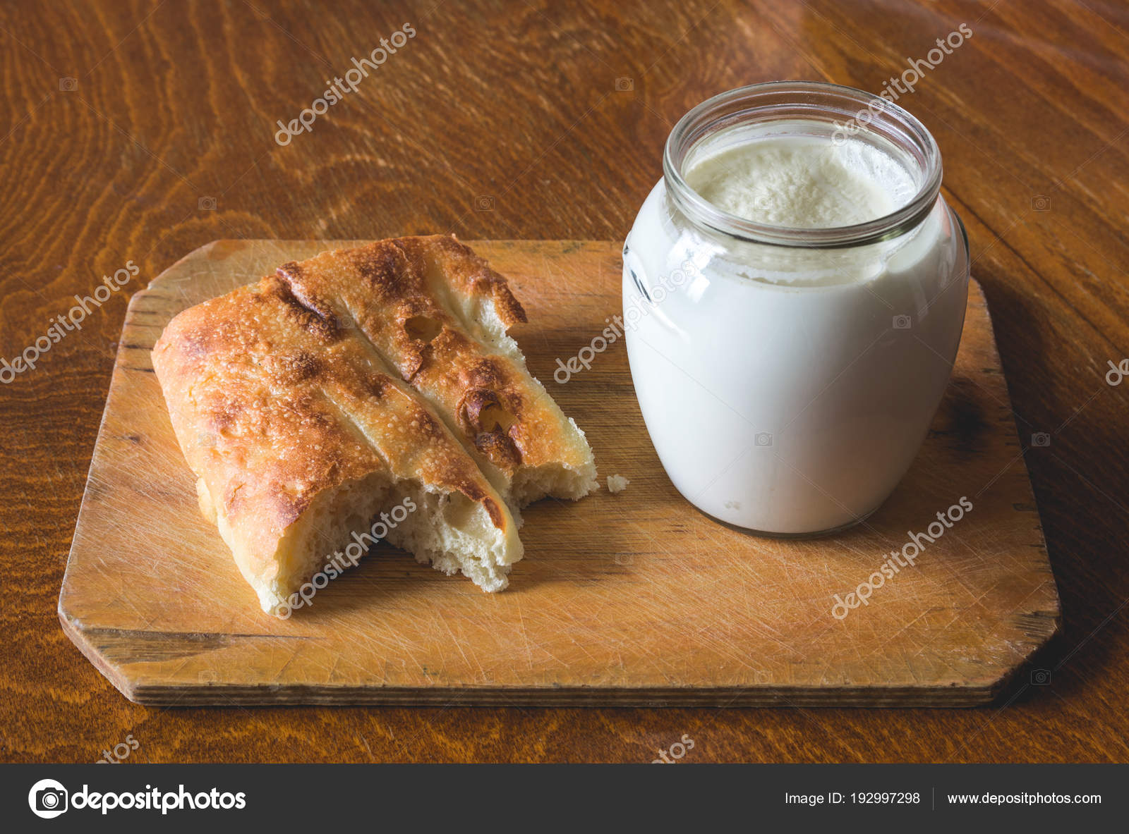 Sour milk in a glass jar with a piece of asian pita bread on