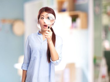 surprised chinese woman with magnifying glass