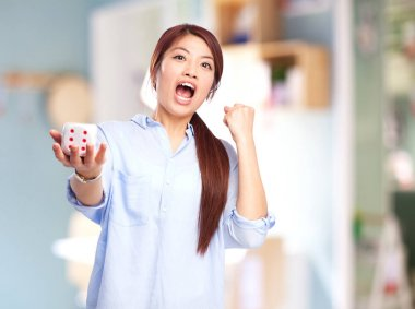 chinese woman with celebrating gesture and dice