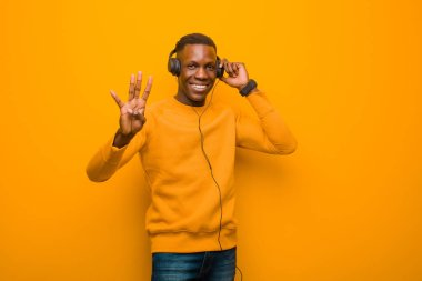 young african american black man against orange wall with headphones