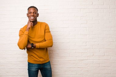 young african american black man smiling happily and daydreaming or doubting, looking to the side against brick wall