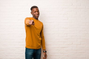 young african american black man pointing at camera with a satisfied, confident, friendly smile, choosing you against brick wall