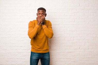 young african american black man looking worried, anxious, stressed and afraid, biting fingernails and looking to lateral copy space against brick wall