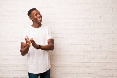 young african american black man feeling happy and successful, smiling and clapping hands, saying congratulations with an applause against brick wall