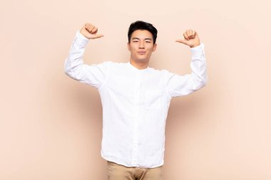 young chinese man feeling proud, arrogant and confident, looking satisfied and successful, pointing to self against flat color wall