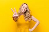 mladá hezká blondýnka se usmívá a vypadá šťastně, bezstarostně a pozitivně, gestikuluje vítězství nebo mír jednou rukou proti ploché barevné stěně
