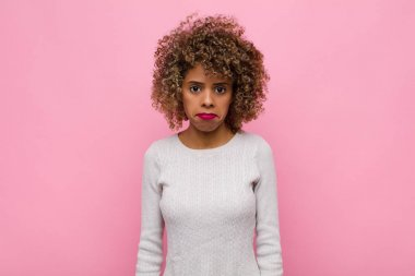 young african american woman feeling sad and whiney with an unhappy look, crying with a negative and frustrated attitude against pink wall