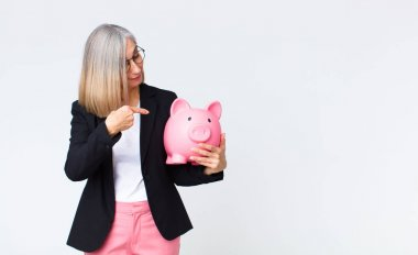 middle age woman with a piggy bank. savings concept