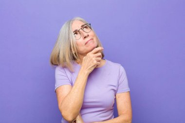 senior or middle age pretty woman thinking, feeling doubtful and confused, with different options, wondering which decision to make