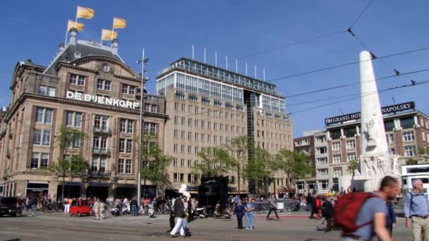 Lidé chodí na náměstí u přehrady Národní památník v Amsterdamu, Nizozemsko.