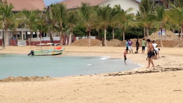 Lidé relaxovat na písečné pláži s palmami v Trincomalee, Srí Lanka